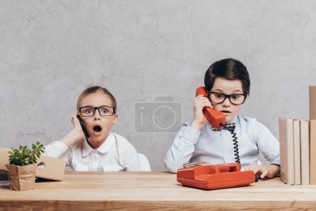 Photo pour Portrait d'enfants choqués parler sur smartphone et téléphone tout en étant assis au milieu de travail - image libre de droit
