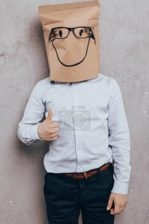 Photo for Kid with paper bag on head shoeing thumb up isolated on grey - Royalty Free Image