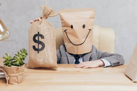 Photo for Kid with paper bag on head holding money bag while sitting at workplace isolated on grey - Royalty Free Image