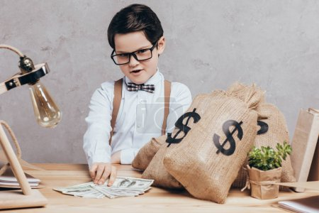 Photo for Little boy sitting at workplace with moneybags and cash isolated on grey - Royalty Free Image