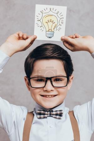 Photo for Portrait of cheerful little boy holding card with light bulb as idea sign in hands isolated on grey - Royalty Free Image