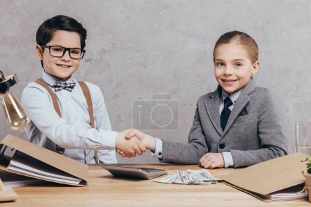 Photo pour Portrait d'enfants caucasiens souriants serrant la main et regardant la caméra sur le lieu de travail - image libre de droit