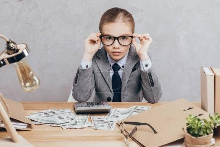 Child calculating money at workplace