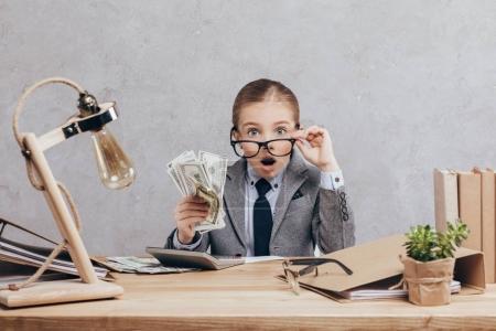 Photo pour Portrait de petite fille choquée avec de l'argent assis sur le lieu de travail avec calculatrice isolée sur gris - image libre de droit