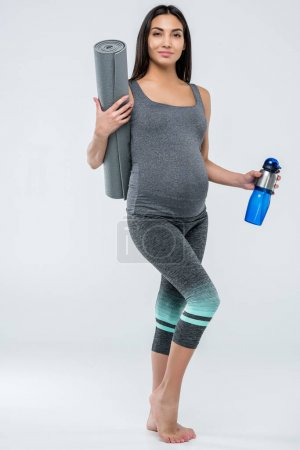Pregnant woman with yoga mat