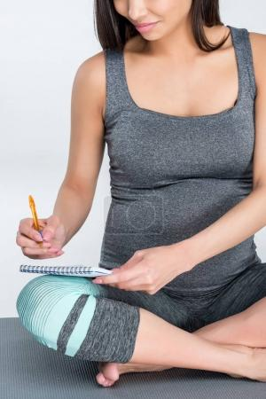 pregnant woman writing in notepad