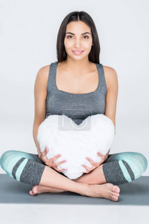 Pregnant woman with heart shaped pillow