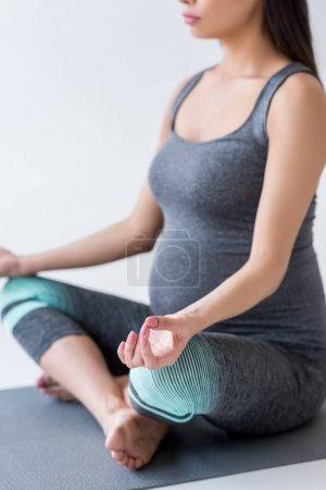 Pregnant woman meditating in lotus pose