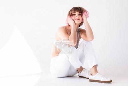 Woman with pink hair sitting on floor