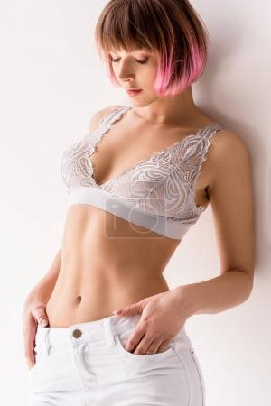 woman in lace bralette and white jeans