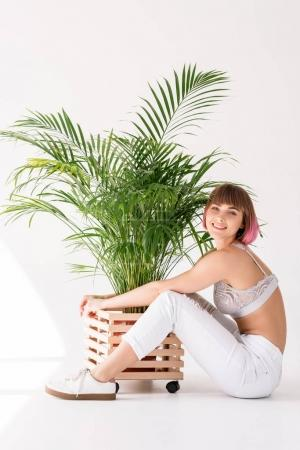 Woman hugging flowerpot with plant