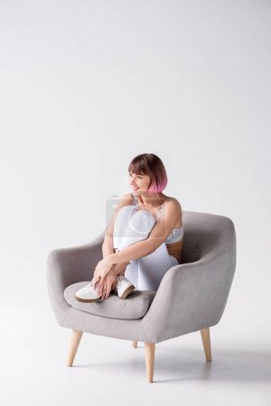 Photo for Young smiling woman with pink hair sitting in armchair and hugging her knees - Royalty Free Image
