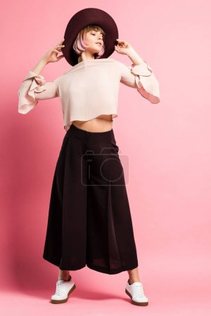 Photo for Full-length shot of young woman in fashionable clothes and wide-brimmed hat posing with arms raised - Royalty Free Image