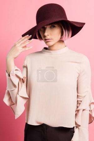 Photo pour Plan à mi-longueur de la jeune femme en vêtements à la mode et chapeau à large bord regardant la caméra, isolé sur rose - image libre de droit