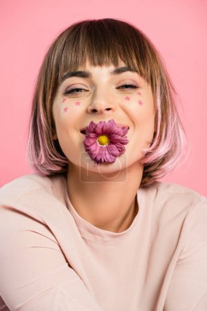 Trendy woman posing with flower in mouth