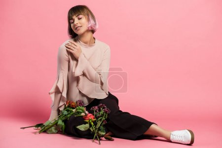 Young woman sitting on floor with bouquet