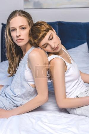 attractive young lesbian couple sitting back to back in bed