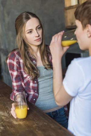 young women drinking fresh orange juice on kitchen