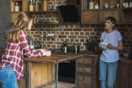 young women talking on kitchen in morning