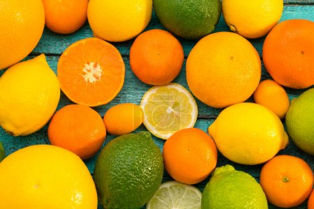 Photo for Top view of various whole and sliced citrus fruits on blue wooden table - Royalty Free Image