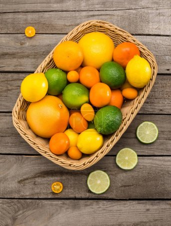 Photo for Top view of various fresh ripe citrus fruits in basket on wooden table - Royalty Free Image