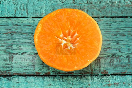Photo for Close-up view of fresh orange slice on blue wooden table - Royalty Free Image
