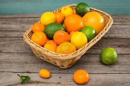 Photo pour Vue rapprochée d'agrumes frais mûrs dans un panier sur une table en bois - image libre de droit