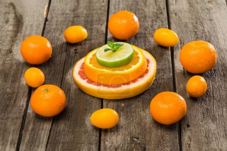 Photo for Variety of citrus fruits slices and tangerines on wooden table - Royalty Free Image