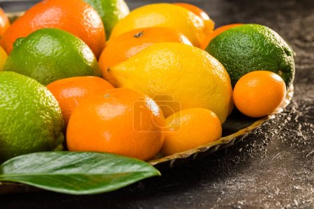 Photo for Side view of fresh whole citrus fruits and leaf on plate - Royalty Free Image