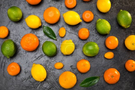Photo for Top view of fresh whole citrus fruits and leaves on black - Royalty Free Image