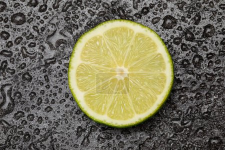 Photo for Close up view of fresh lime slice on black - Royalty Free Image