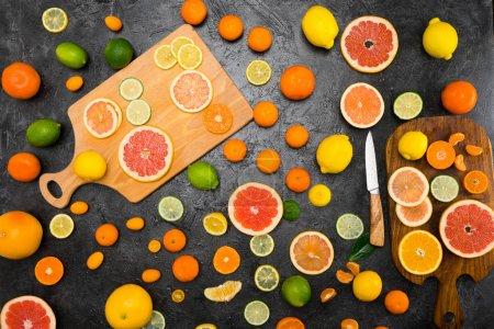 Photo pour Vue de dessus de divers agrumes frais entiers et tranchés sur des planches à découper sur noir - image libre de droit