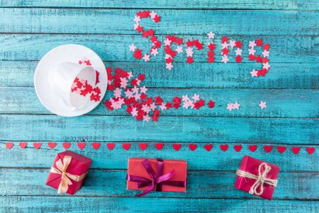 Photo for Top view of springtime composition with stars falling out cup, gifts and spring lettering on wooden table - Royalty Free Image