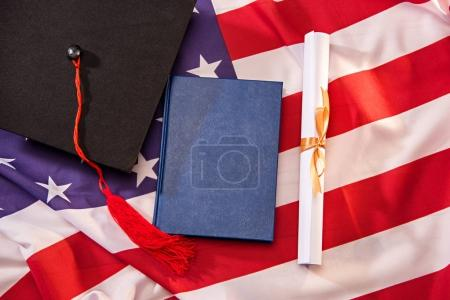 graduation cap and diploma on usa flag