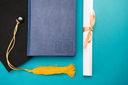 Photo pour Vue du dessus du livre, du chapeau de graduation et du diplôme sur le bleu, concept d'éducation - image libre de droit
