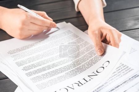 Photo pour Recadrée vue de femme d'affaires, signature des documents contractuels, assis à table - image libre de droit
