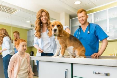 Woman, daughter with dog at veterinary doctor