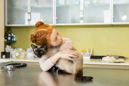 girl embrace her cat at veterinary clinic