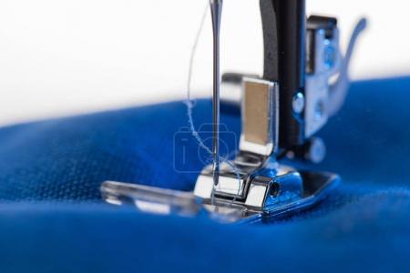 Photo pour Vue rapprochée de travail machine à coudre couture tissu bleu - image libre de droit