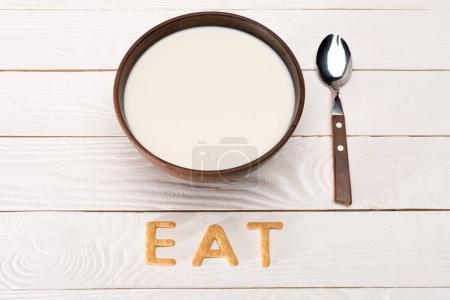 Photo for Close-up view of milk in bowl, spoon and word eat from breakfast cereal letters on wooden table top - Royalty Free Image