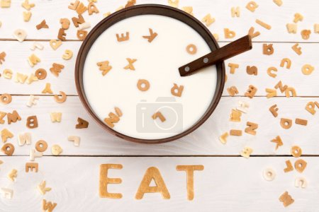 Photo for Close-up view of milk and spoon in bowl, word eat from breakfast cereal letters and alphabet corn flakes on wooden table - Royalty Free Image