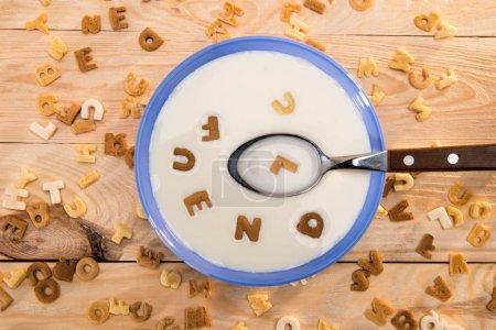 Photo pour Vue de dessus du bol avec le lait et la cuillère et alphabet de flocons de maïs sur la table en bois - image libre de droit
