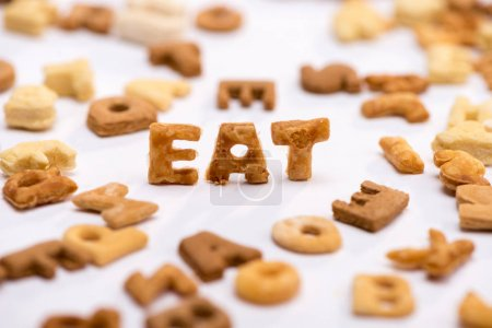 Photo for Close-up view of word eat and healthy breakfast cereal alphabet isolated on white - Royalty Free Image