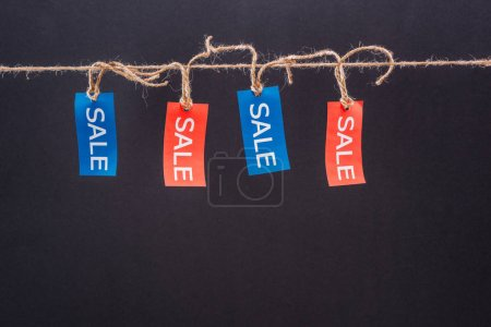 Photo for Close-up view of red and blue sale tags hanging on rope isolated on black, Offer sale tags - Royalty Free Image