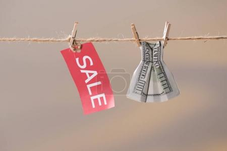 sale sign and dollar banknote on clothesline