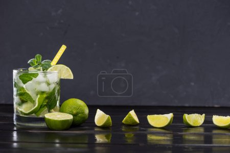 Photo for Close-up view of mojito cocktail with straw in glass and lime slices on black, cocktail drinks concept - Royalty Free Image
