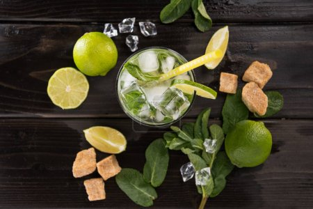 Photo for Top view of mojito cocktail in glass and fresh ingredients on dark wooden table top, cocktail drinks concept - Royalty Free Image