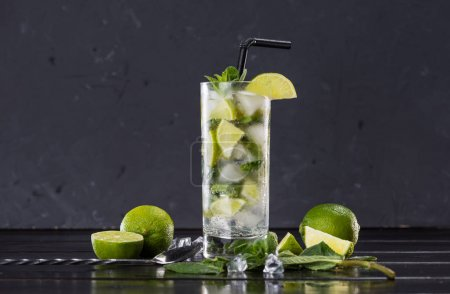 Photo for Close-up view of mojito cocktail in glass, sliced limes and mint on black, cocktail drinks concept - Royalty Free Image