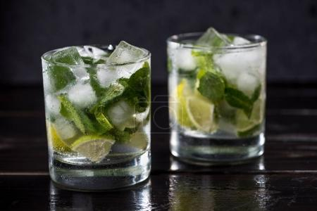Photo for Close-up view of mojito cocktail in glasses on dark wooden table, cocktail drinks concept - Royalty Free Image