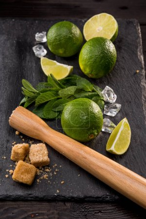 Lime slices with sugar and wooden squeezer